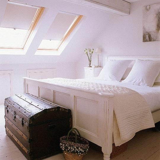 all white attic bedroom with skylights and a gorgeous trunk