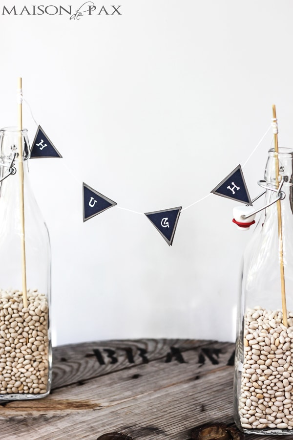 glass bottles hold navy and gray bunting with white letters | Maison de Pax