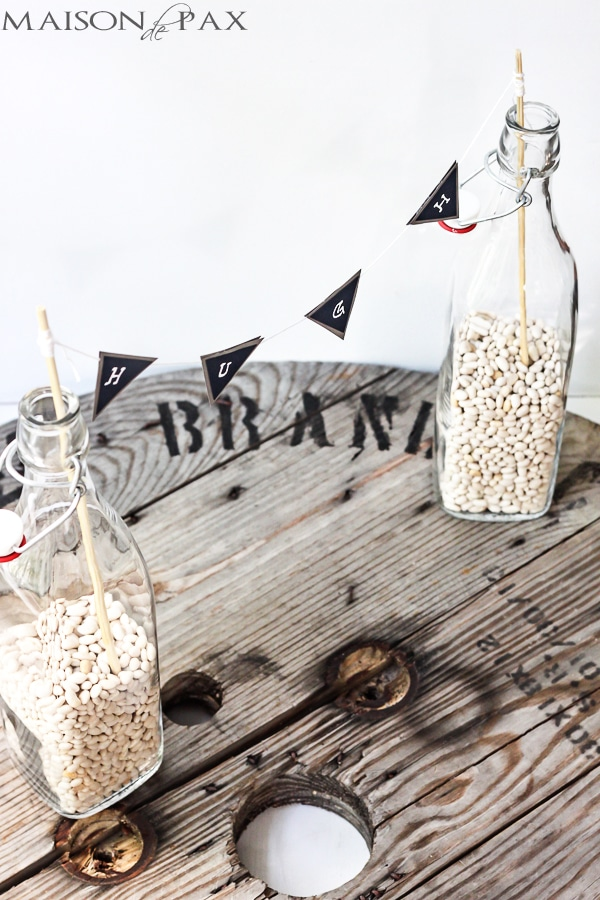dried white beans anchor sticks in glass bottles to hold paper bunting | Maison de Pax