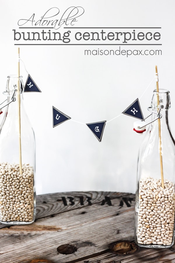 bunting between two bottles with overlay: adorable bunting centerpiece | Maison de Pax