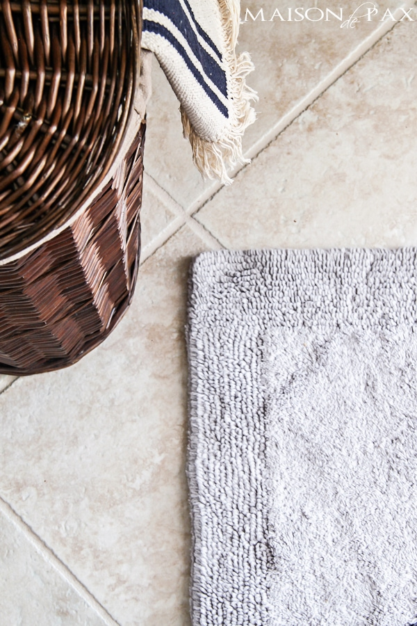 Close-up view of neutral tile bathroom floor and organic bath mat- Maison de Pax