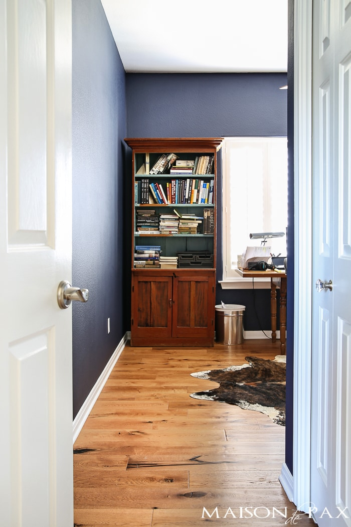 deep navy blue office with rustic wood floors, lots of bookcases, and an eclectic, collected vibe