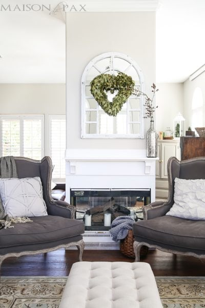 beautiful, neutral living room with gray wingback chairs, natural textures, white fireplace, and a gorgeous wreath