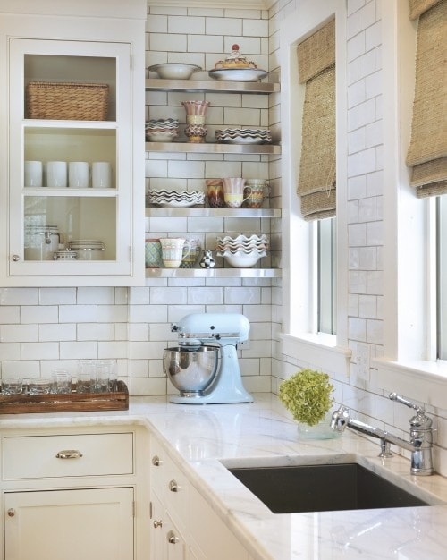 all white kitchen: cabinets, marble countertop, and white subway backsplash