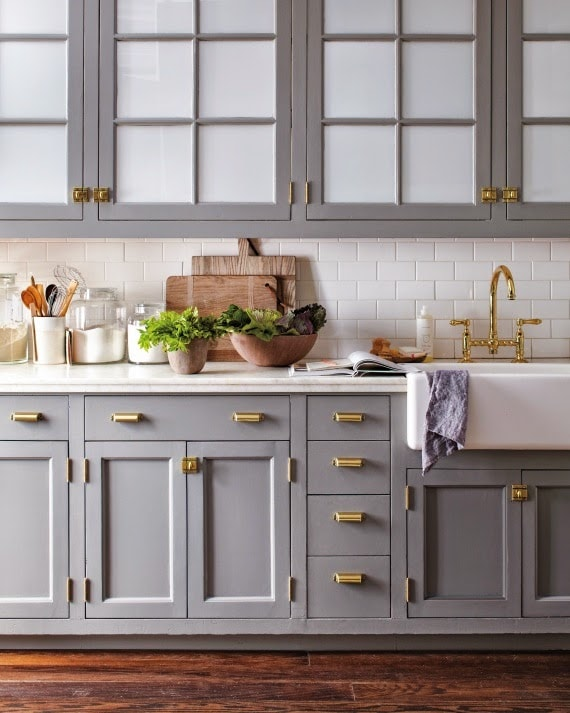 gray cabinets with white subway tile backsplash and brass hardware