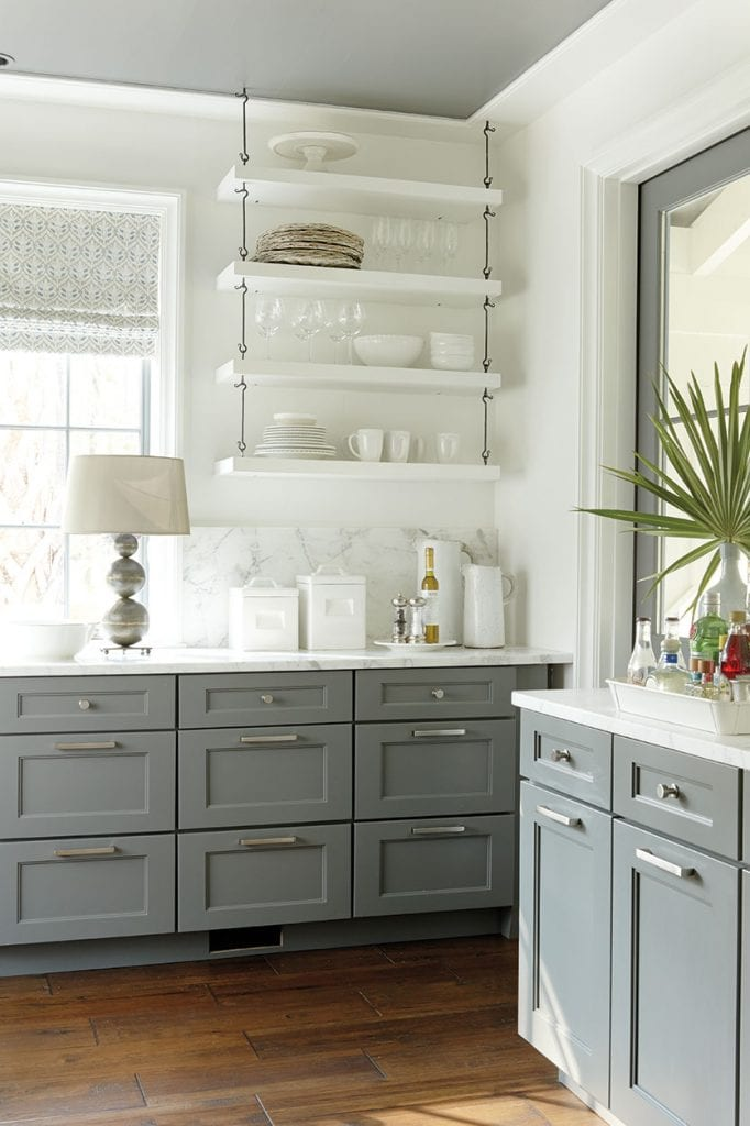 kitchen with gray lower cabinets and open white floating shelves