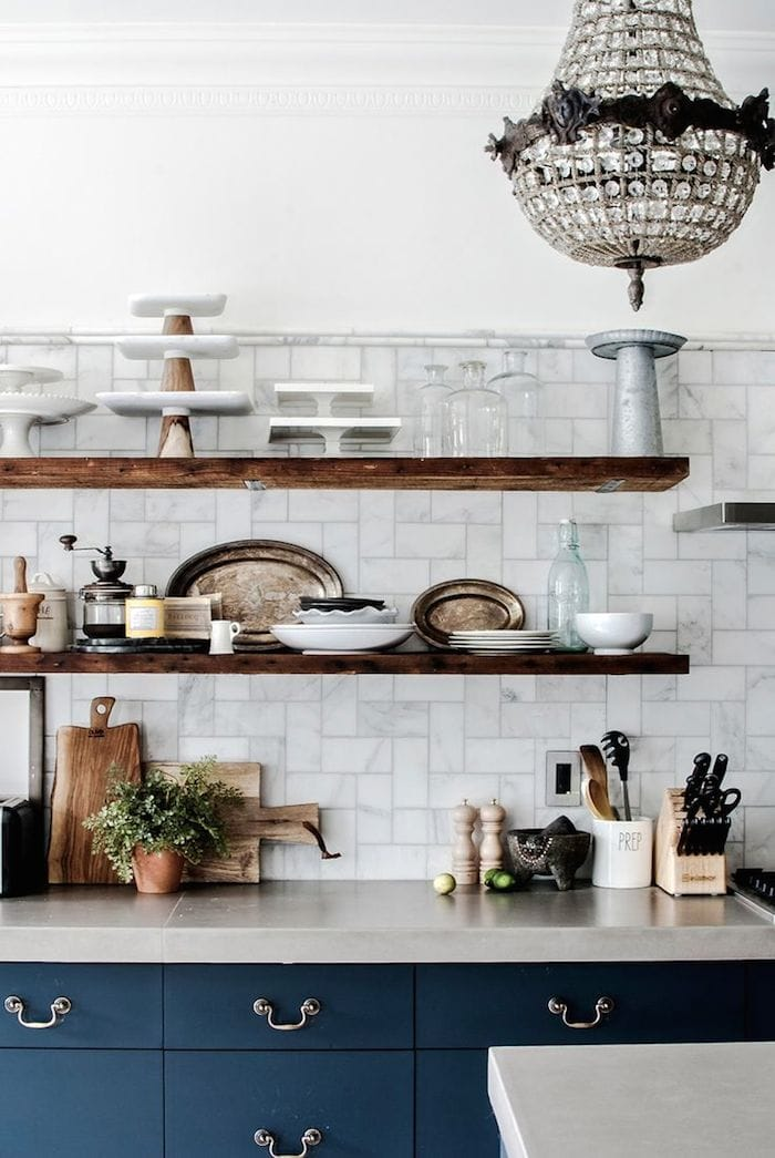 navy lower cabinets, open rustic wood floating shelves, marble backsplash