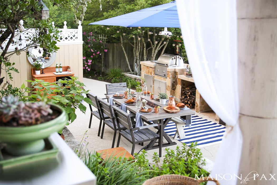 Outdoor living space with umbrella and grill- Maison de pax