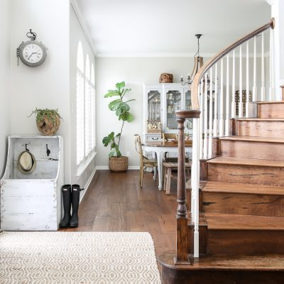 simple, modern farmhouse entryway with neutral textures, smart storage, and a gorgeous wooden staircase #simpleentry #entrydesign #entrydecor #entrywaydesign #neutraldecorating #modernfarmhouse #frenchcountry