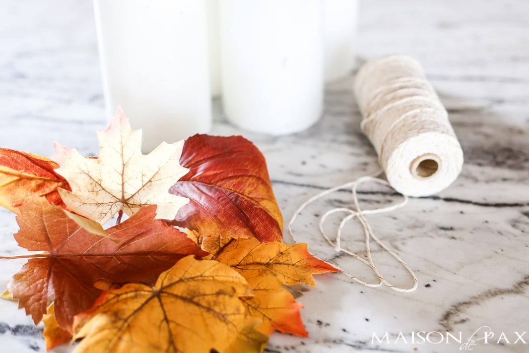 fall craft idea: white pillar candles, fall leaves, baker's twine