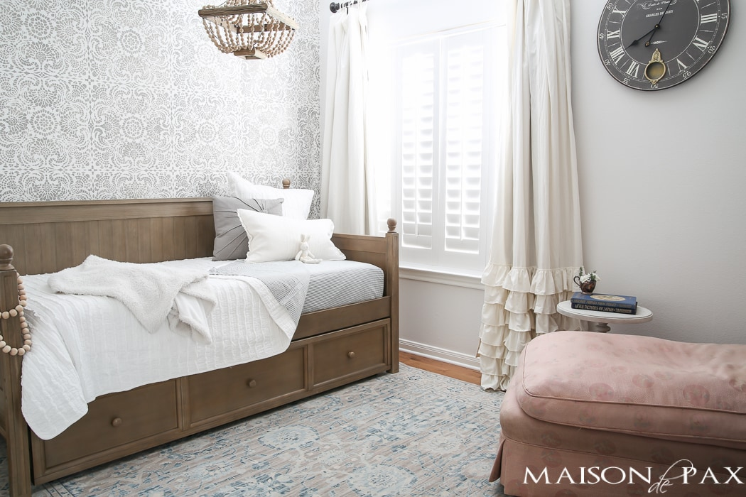 Elegant, neutral little girl room with wood tones and a stenciled accent wall: A gray-washed trundle bed provides the perfect anchor for a gorgeous, neutral yet feminine little girl's room.