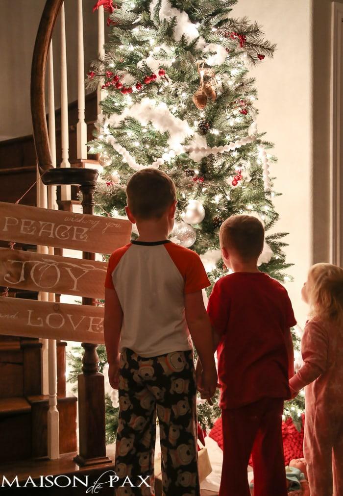 Kids in front of lit Christmas tree- Maison de Pax