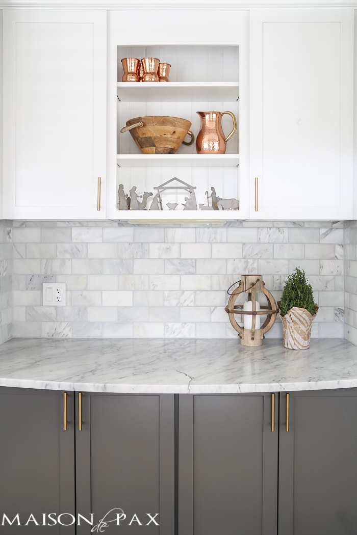 Gorgeous two-tone kitchen design with white upper cabinets, gray lower cabinets, carrara marble counters and marble subway tile backsplash- Maison de Pax