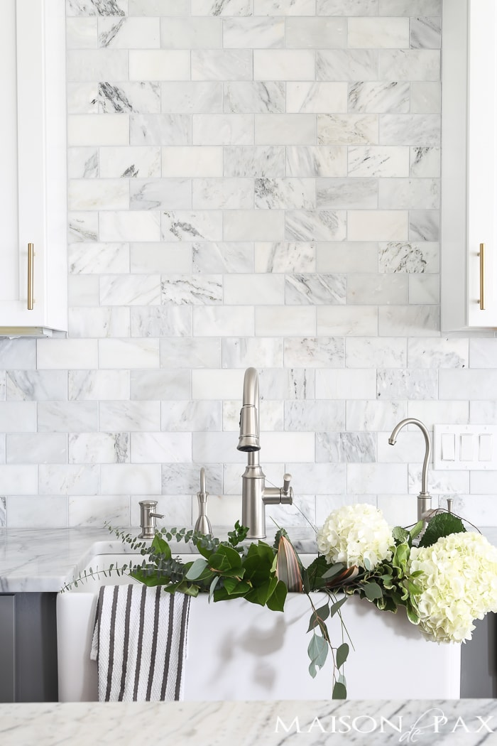 Should I use marble in the kitchen?  It's one of the most common questions for today's kitchen design!  Read all about the pros and cons of marble countertops as well as what it is like living with honed marble countertops in a household with kids. #carraramarble #marblebacksplash #marblecountertops #marblecounters #marblekitchen