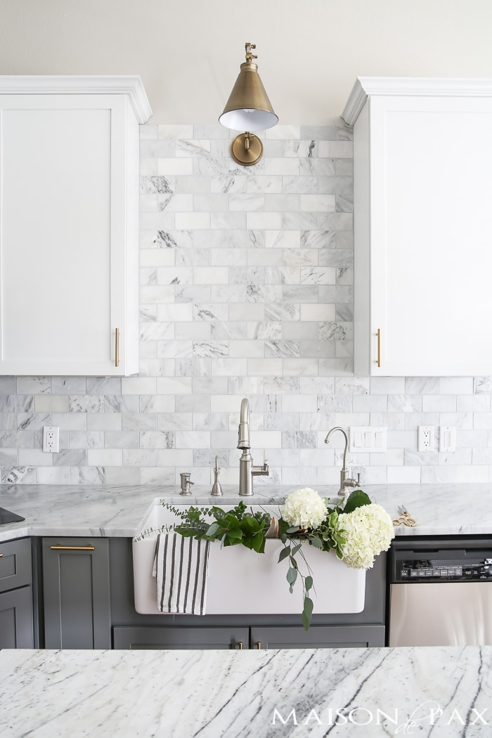 Two-toned gray and white cabinets, marble subway tile, Carrara countertops, a big farmhouse sink, and brass hardware... Find out how to care for marble kitchen countertops with these five tips! #marble #marblekitchen #marblecounters #marblebacksplash #marblecountertops