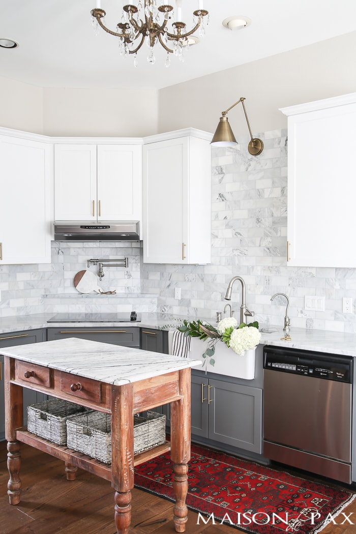 marble island, backsplash, and countertops in a gray and white kitchen- Maison de Pax