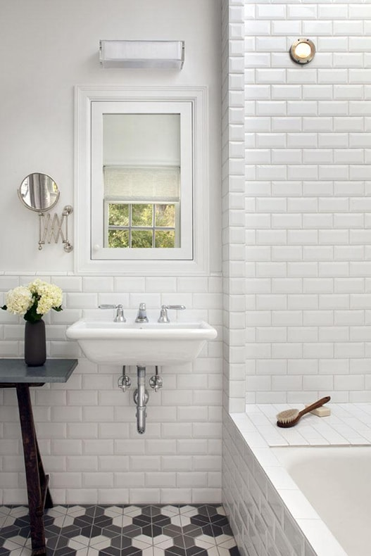 Remodelista: classic white cottage bathroom with beveled white subway tile and patterned black and white concrete tile floors