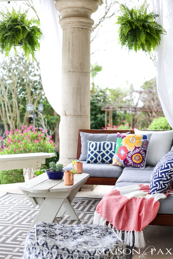 Outdoor patio space with Boston ferns and cushioned furniture styled for spring- Maison de Pax