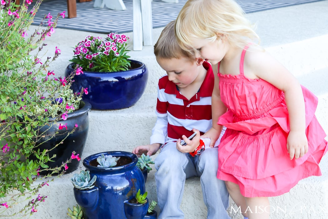two small children sitting on a painted porch with spring planters- Maison de Pax