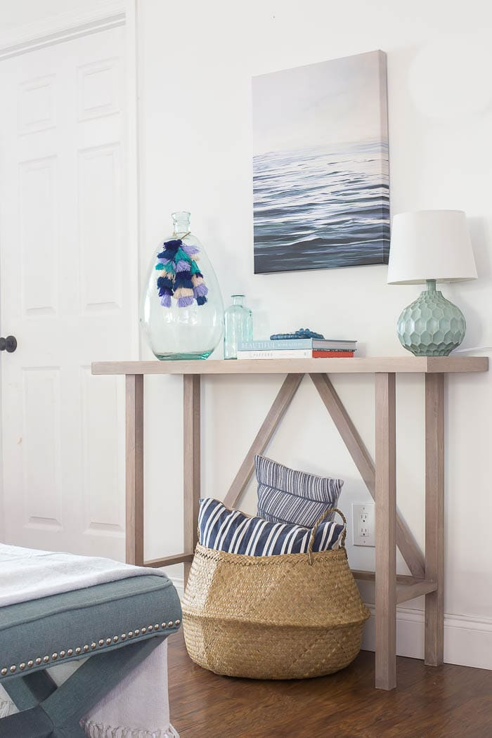 What a fun beachy vibe in this coastal living room! Blues, greens, weathered wood, and DIY wall art make it a beautiful, comfortable space.