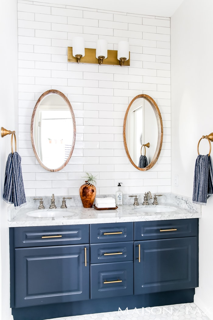 navy and brass Jack and Jill bathroom with white subway tile, gold lighting and hardware, and a polished nickel sink faucet - Maison de Pax