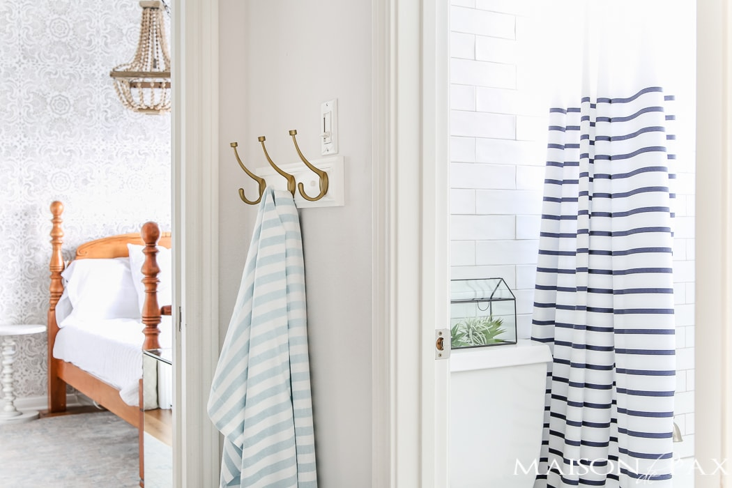 love the crisp navy and white bathroom against the patterned gray bedroom wall