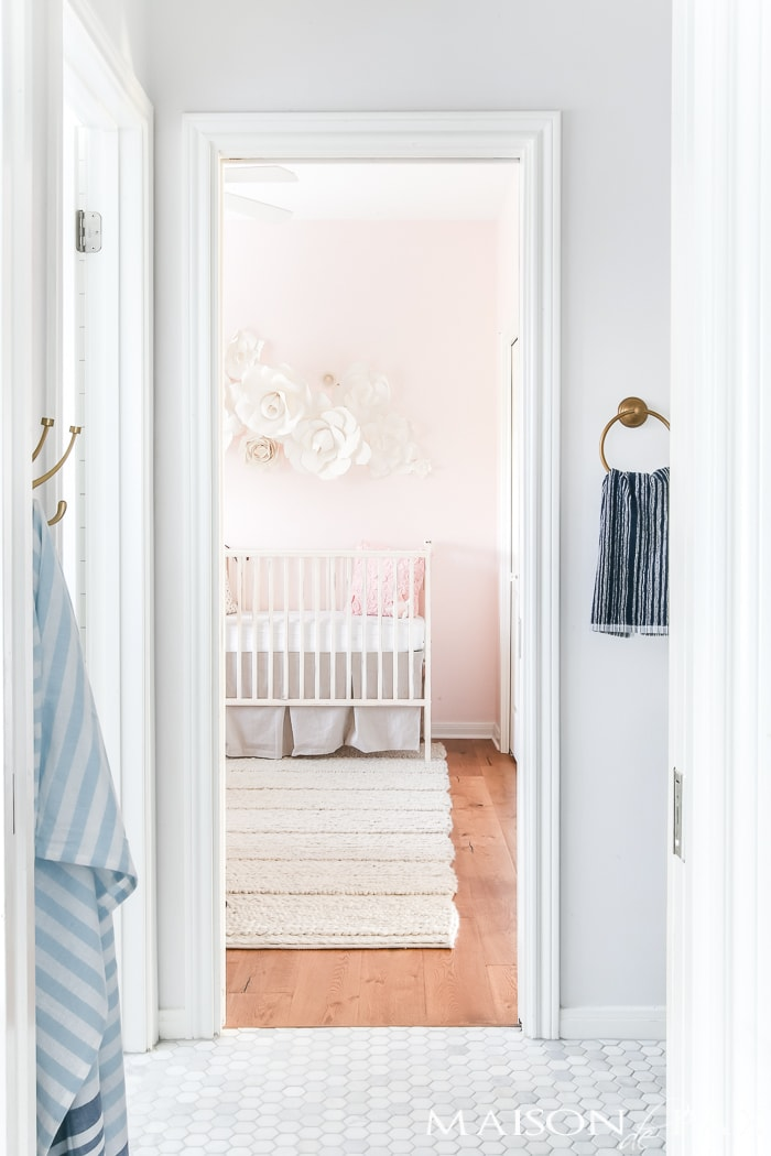 marble white and navy bathroom next to a blush nursery