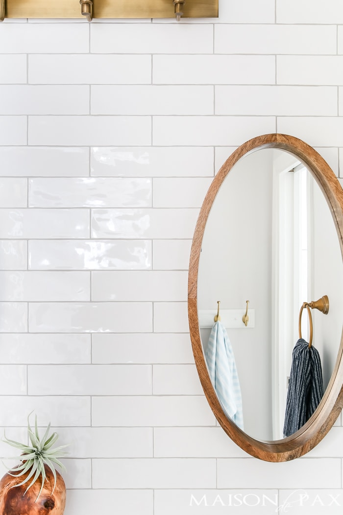 wood mirror against glossy white tile
