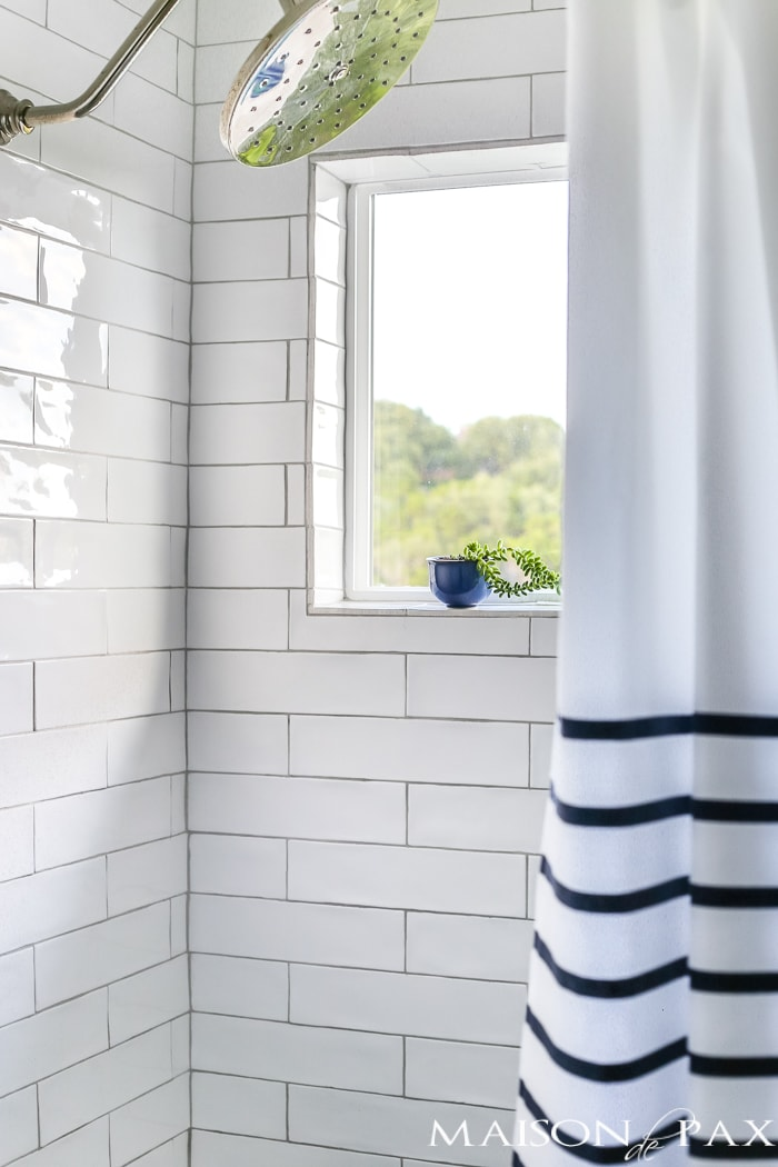 succulents on the shower ledge - brilliant! And love the navy and white striped shower curtain