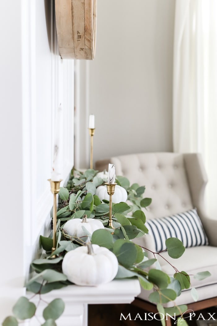 silver dollar eucalyptus and white pumpkins and brass candlesticks make elegant neutral fall decor
