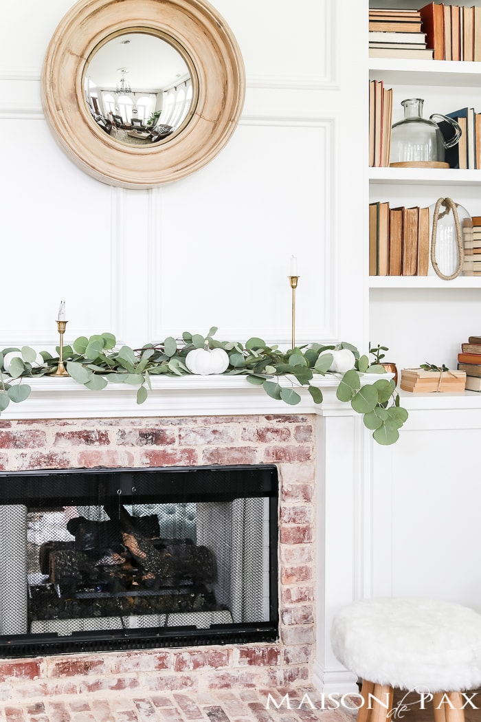 white pumpkins, brass candlesticks, and eucalyptus make a gorgeous fall mantel #fallmantel
