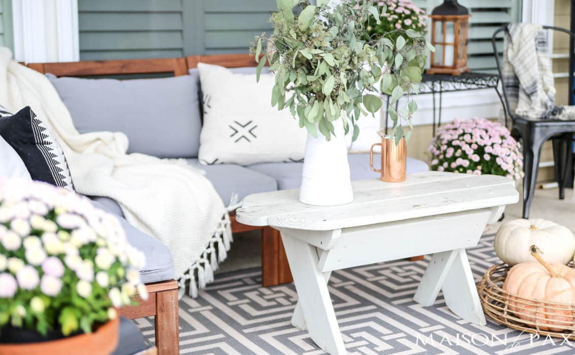 Neutral Pillows And Pastel Pumpkins Make A Cozy Fall Porch