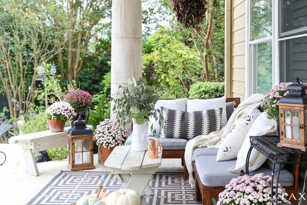 cozy fall porch with neutral textures, wooden lanterns, and pink mums