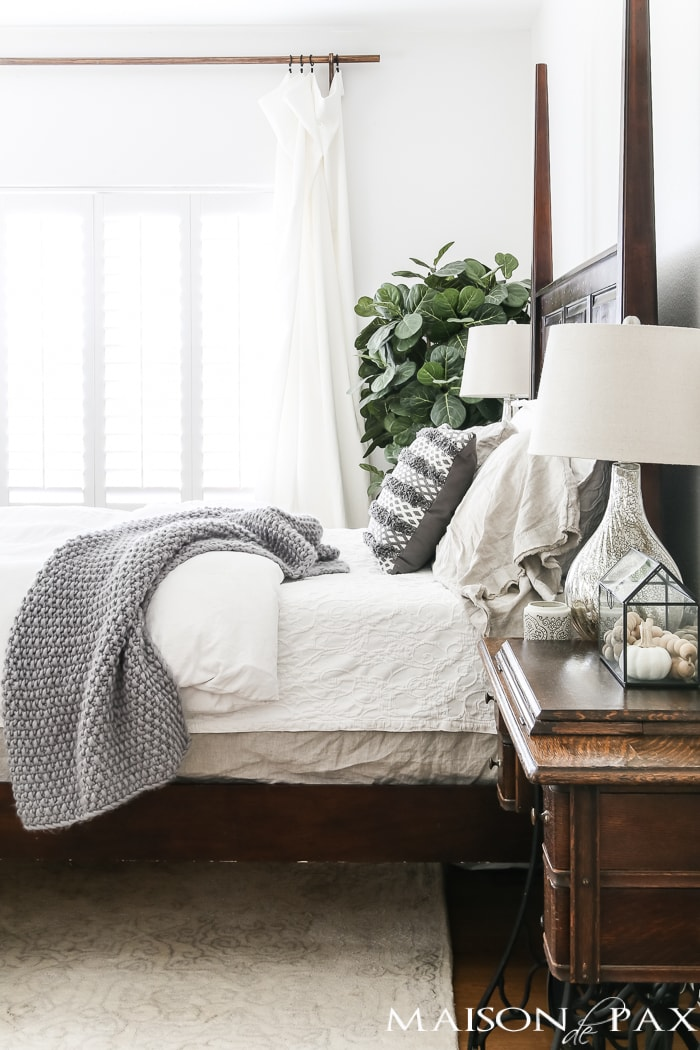 four poster wood bed is offset with white bedding and gray accents- Maison de Pax