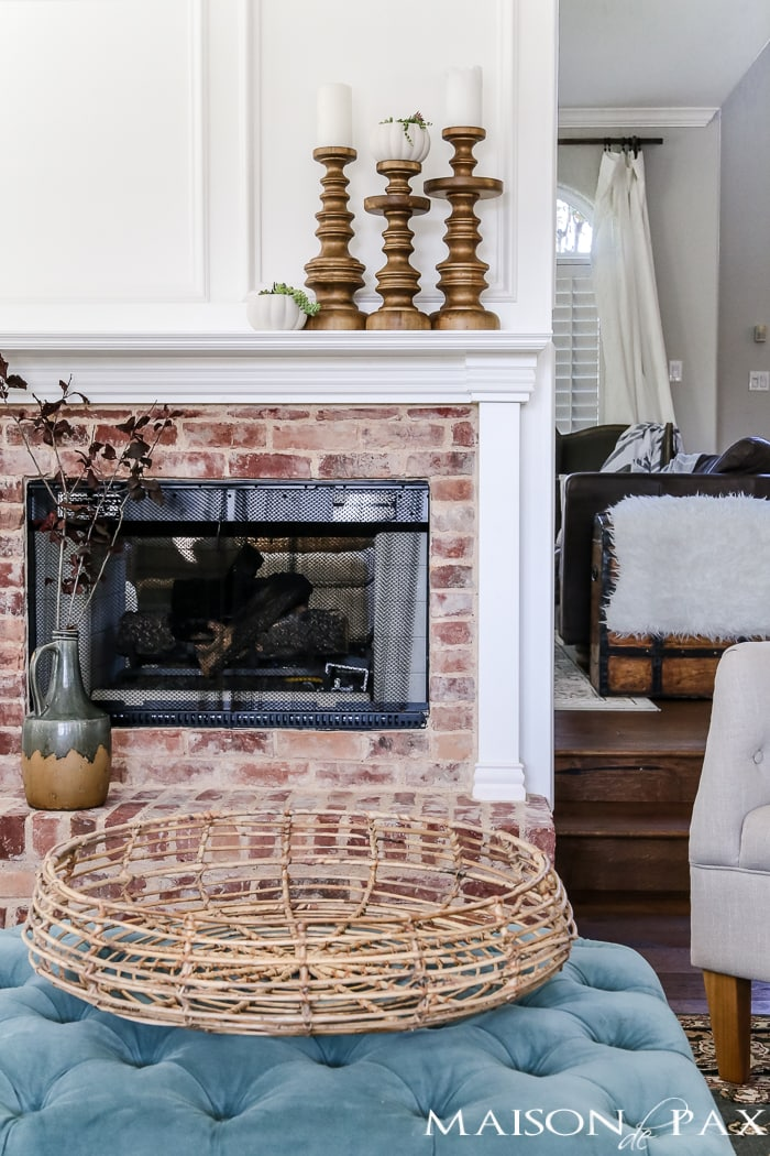 simple, neutral fall mantel decor ideas: woven basket, wood candlesticks, and glazed pitcher
