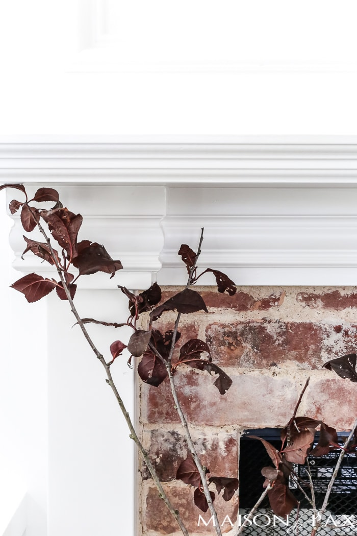simple, neutral fall mantel decor ideas: fall leaves in a glazed pitcher
