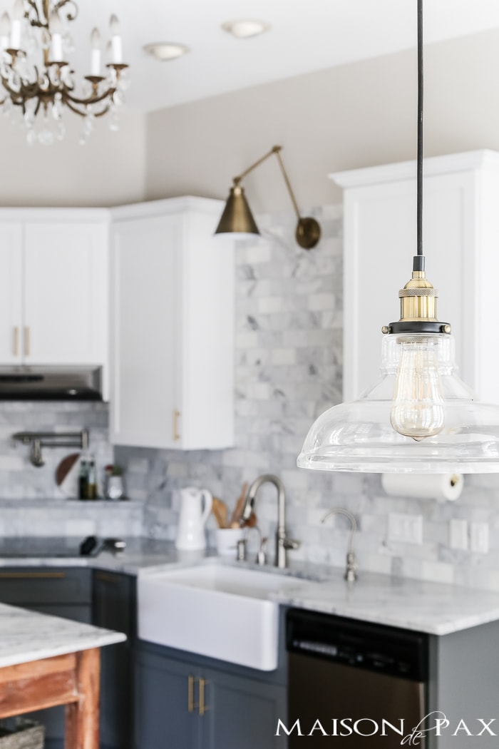 glass and brass industrial pendant light is perfect for a modern touch in this marble white kitchen #kitchenlighting