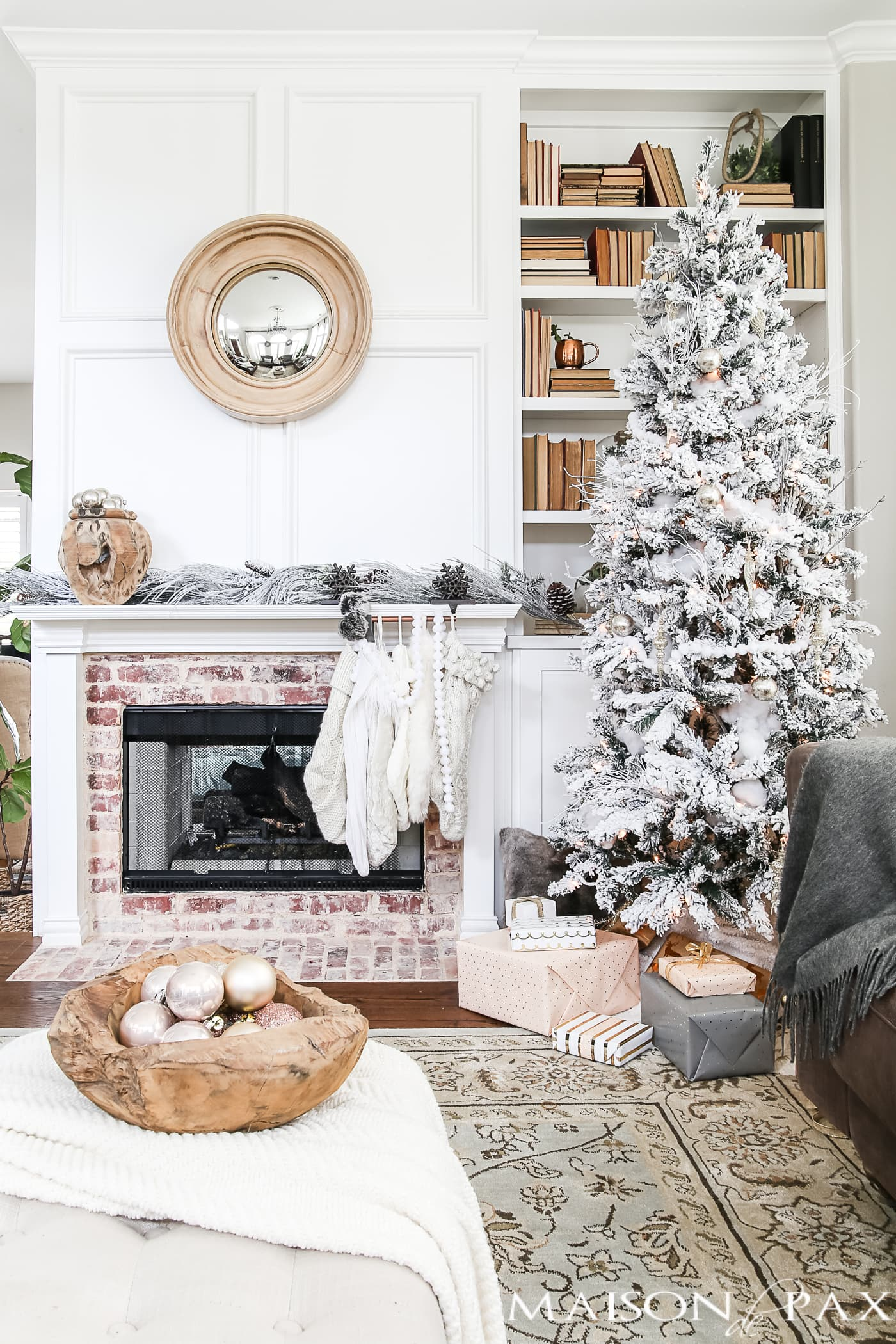 flocked tree with neutral decorations beside a mantel with cream and white stockings #neutralChristmasdecor
