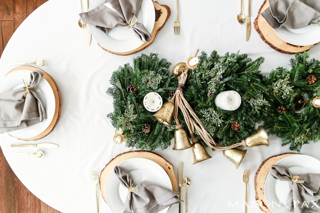 natural centerpiece of green wreaths and brass candelsticks #holidaycenterpiece