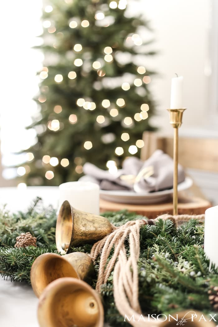 gold sleigh bells and green wreaths and brass candlesticks for a holiday centerpiece #holidaytablescape