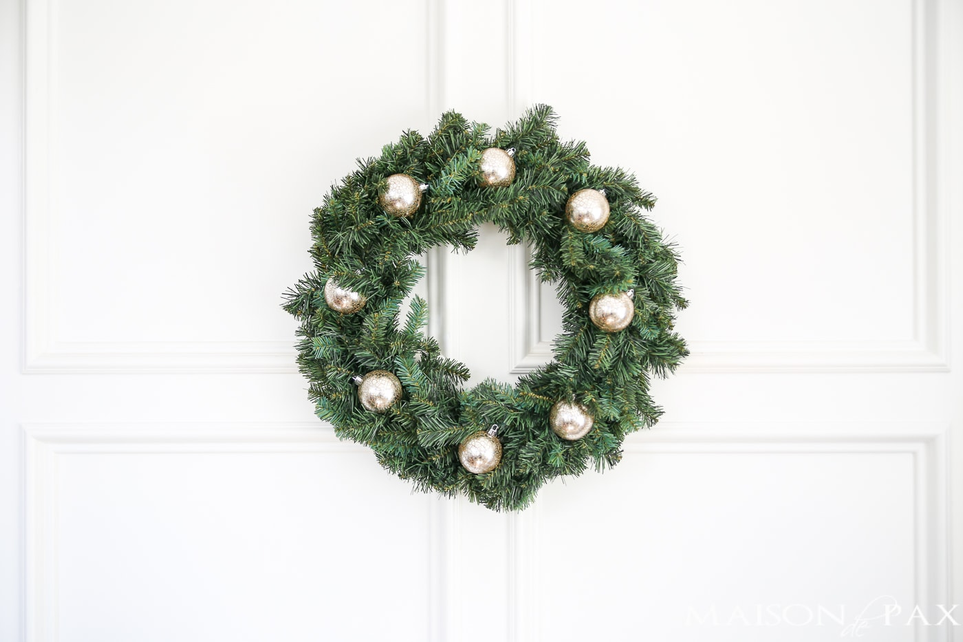 insert a few ornaments into a cheap wreath to great a gorgeous, expensive look (and click for 4 other easy, affordable wreath ideas!) #christmaswreath