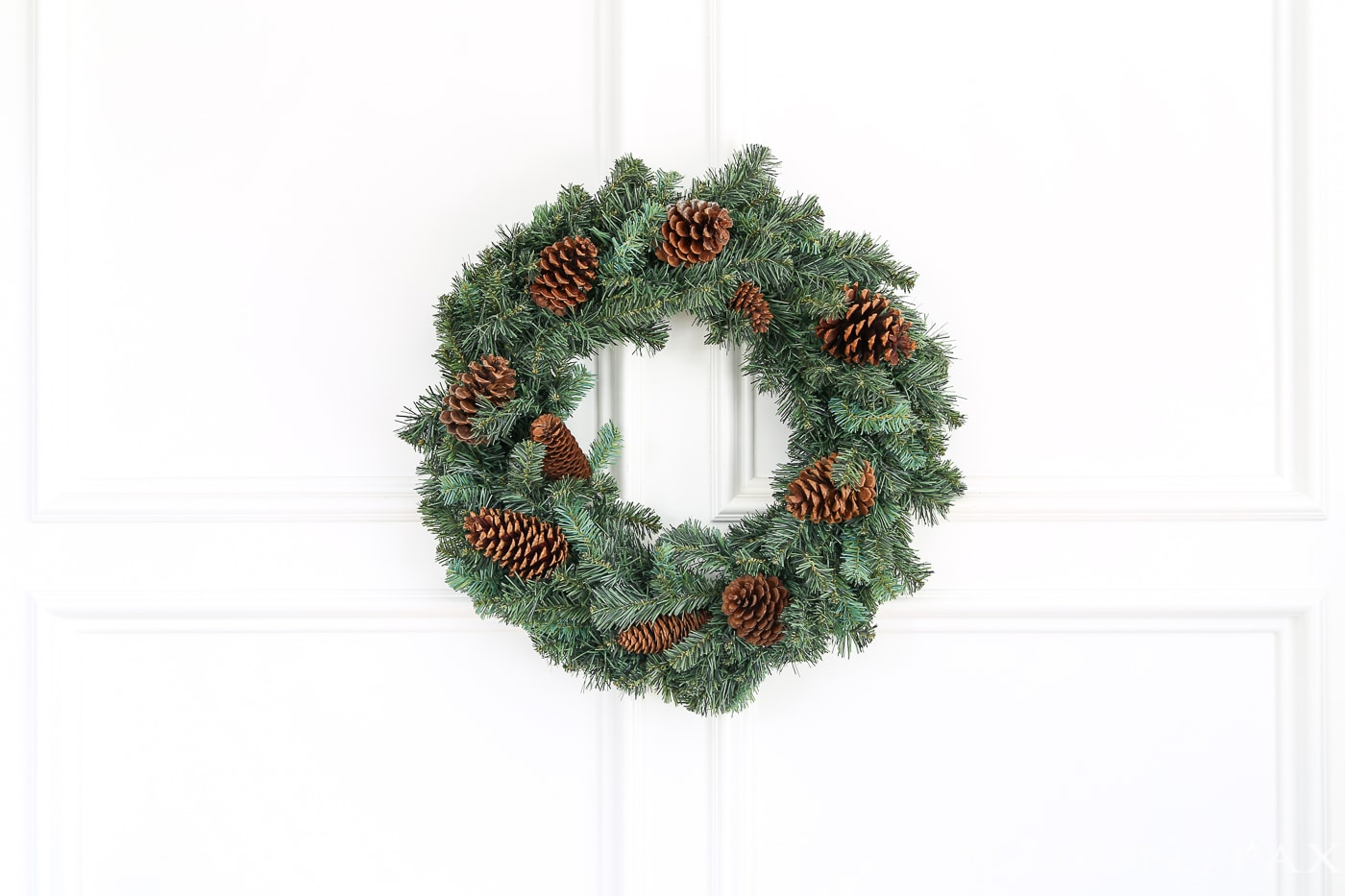 insert pine cones into a cheap wreath to great a gorgeous, expensive look (and click for 4 other easy, affordable wreath ideas!) #christmaswreath
