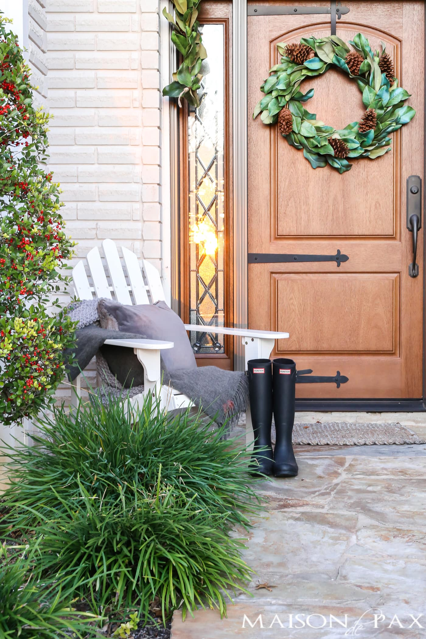 adirondack chair, gray throw, velvet pillow, and hunter boots make a cozy scene for a winter porch #winterporch