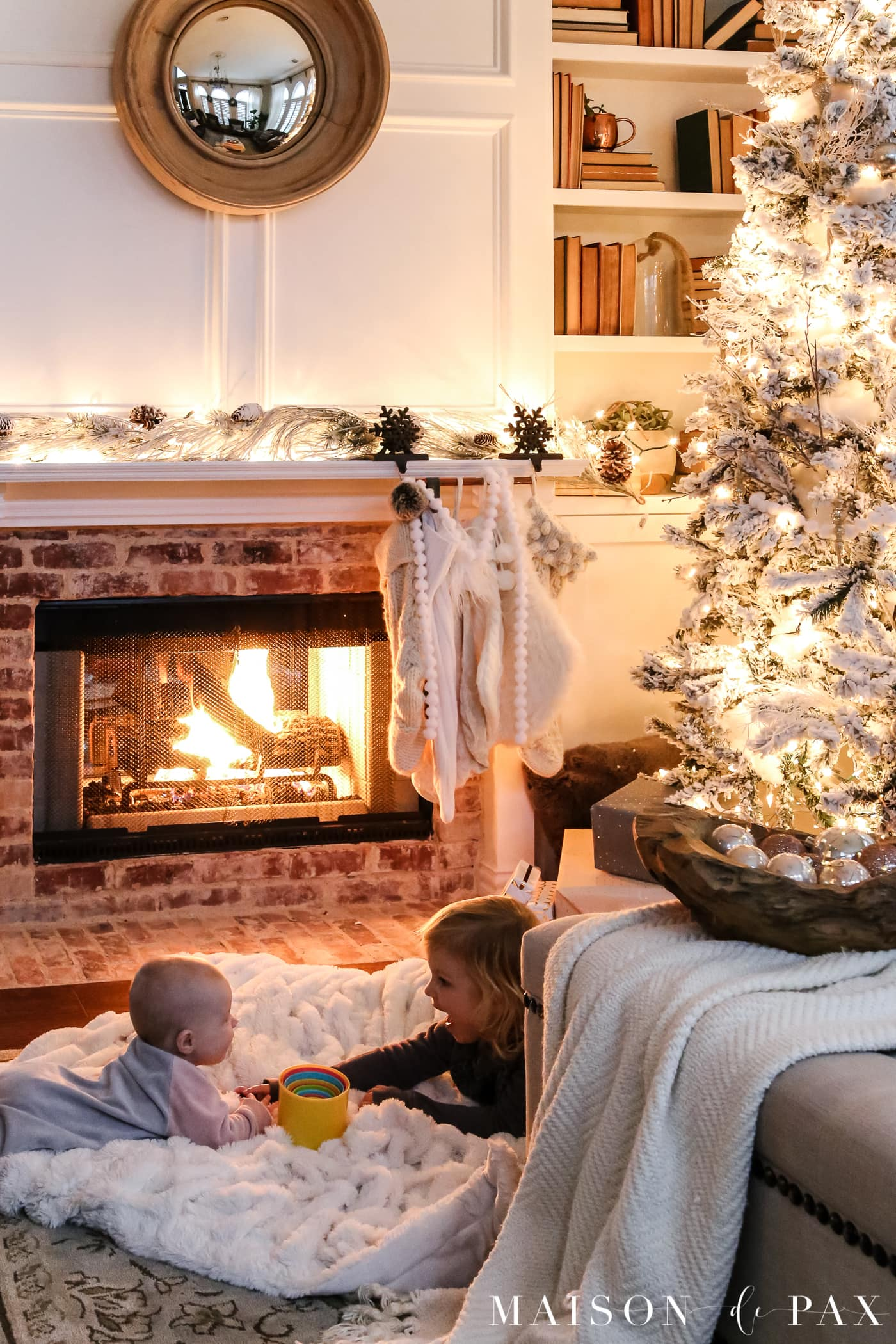 sweet little girls beside the fireplace: gorgeous Christmas lights at night in these 25+ home tours #christmasnightstour #holidayhometour #christmaslights