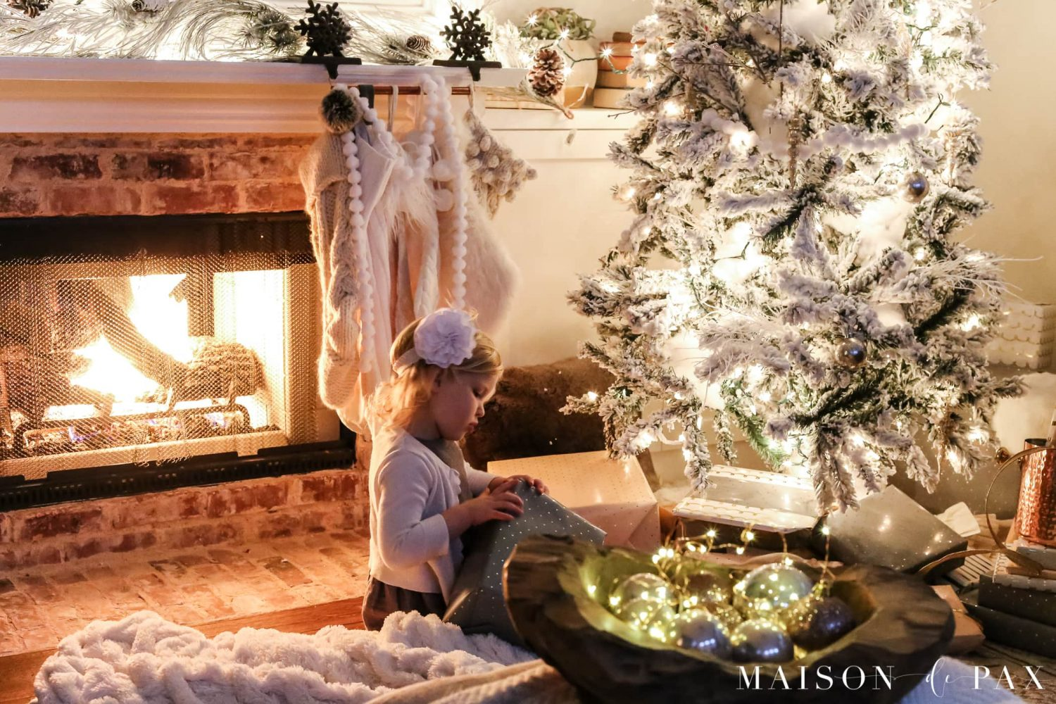 girl opening presents beside Christmas tree in front of roaring fire | Maison de Pax