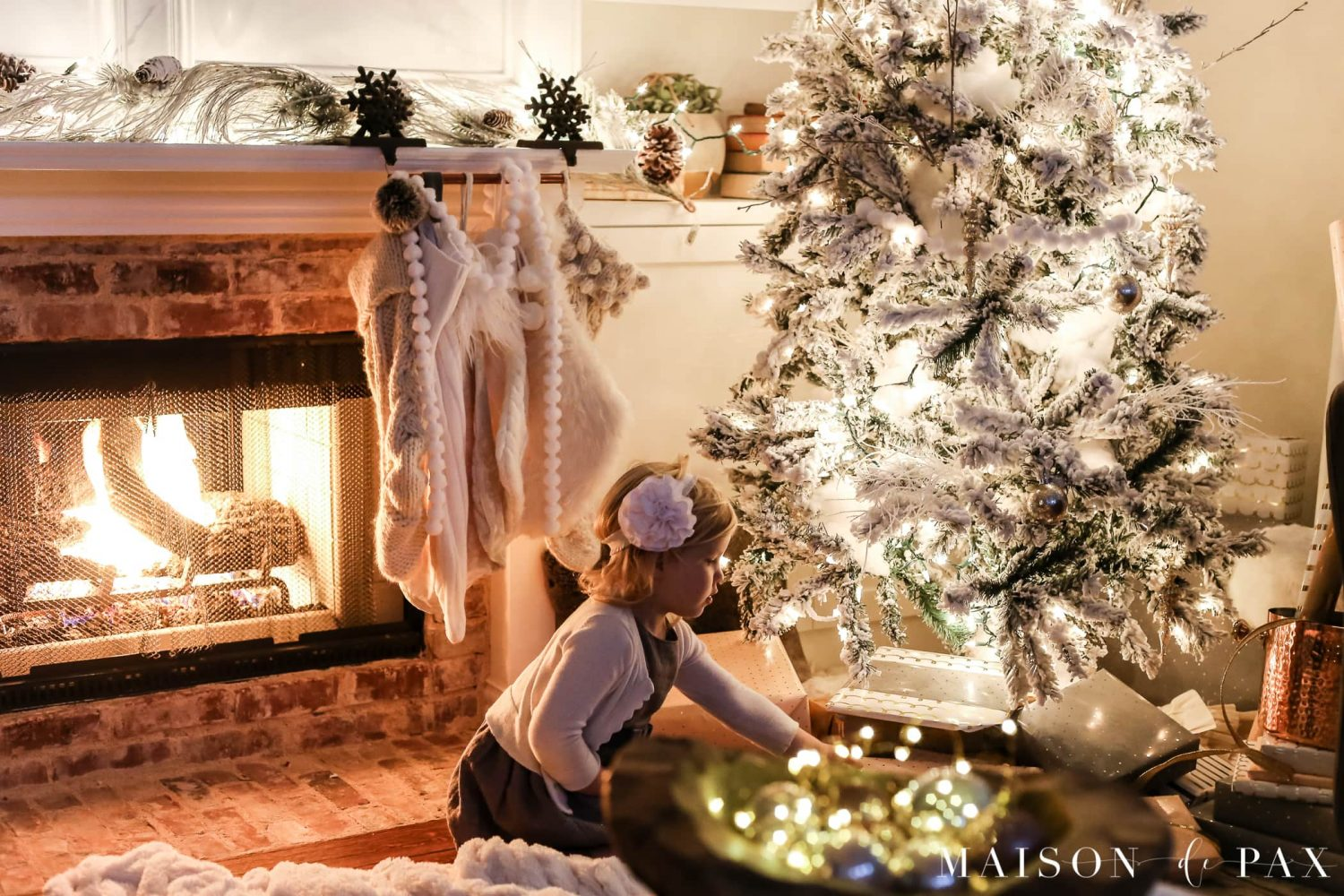 sweet photo of little girl by Christmas tree: gorgeous Christmas lights at night in these 25+ home tours #christmasnightstour #holidayhometour #christmaslights