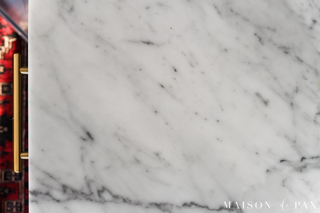 scratches on marble countertops: Should I use marble in the kitchen?  It's one of the most common questions for today's kitchen design!  Read all about the pros and cons of marble countertops as well as what it is like living with honed marble countertops in a household with kids. #carraramarble #marblebacksplash #marblecountertops #marblecounters #marblekitchen