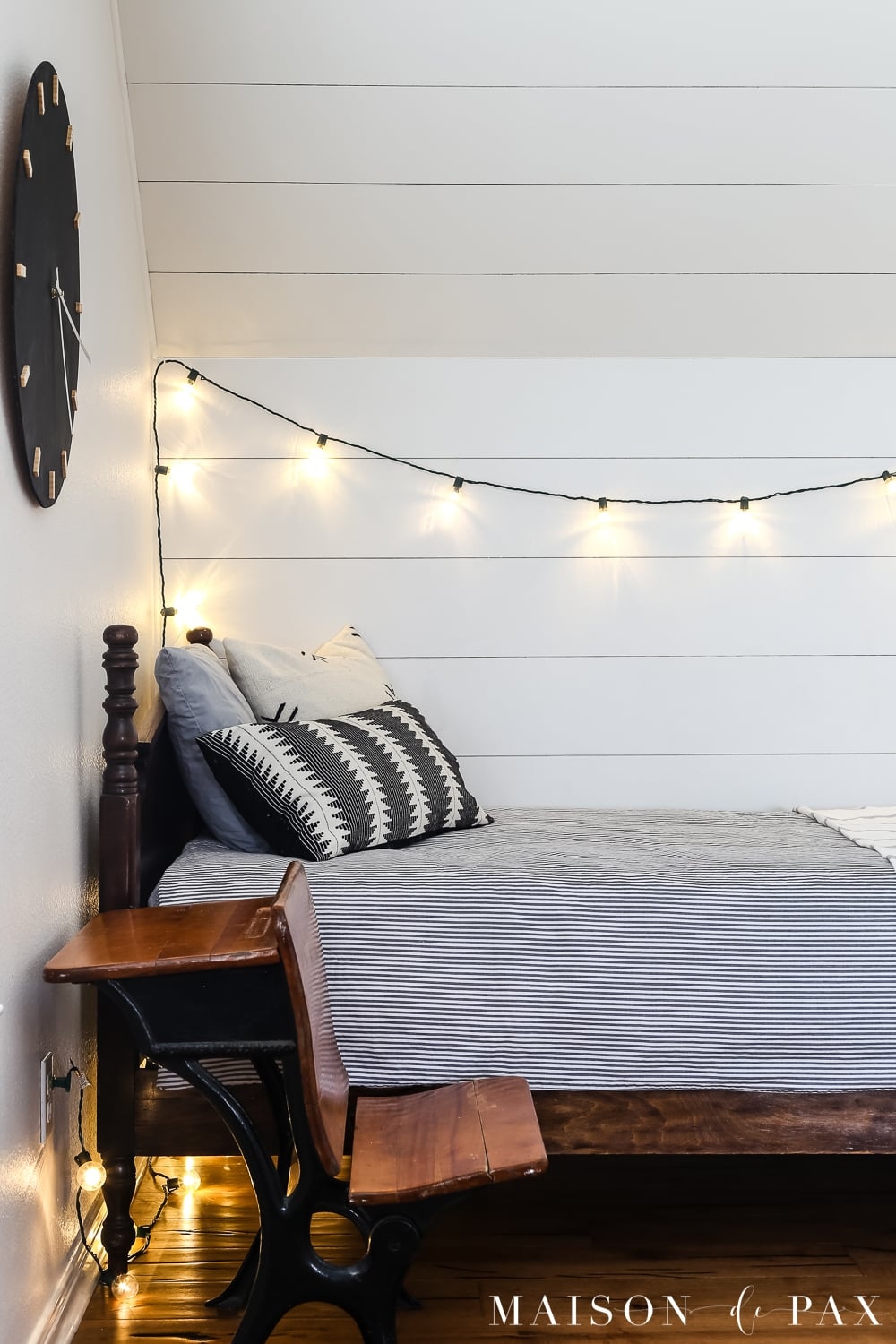 Plastic globe lights and wood wall clock for a boy's bed nook!  Learn how to make this DIY black and wood giant wall clock for cheap! #wallart #diywallart #diyclock #wallclock #giantclock #modernfarmhouse #neutraldecor #kidsroom #boyroom #modernfarmhouse #blackandwhiteinteriors