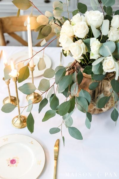 white roses and eucalyptus centerpiece make a gorgeous, simple spring table - perfect for Easter, Valentines Day, or any celebration #eastertable #springtable #tablescape #eucalyptus #centerpiece #vintagechina #goldflatware #easterdecor