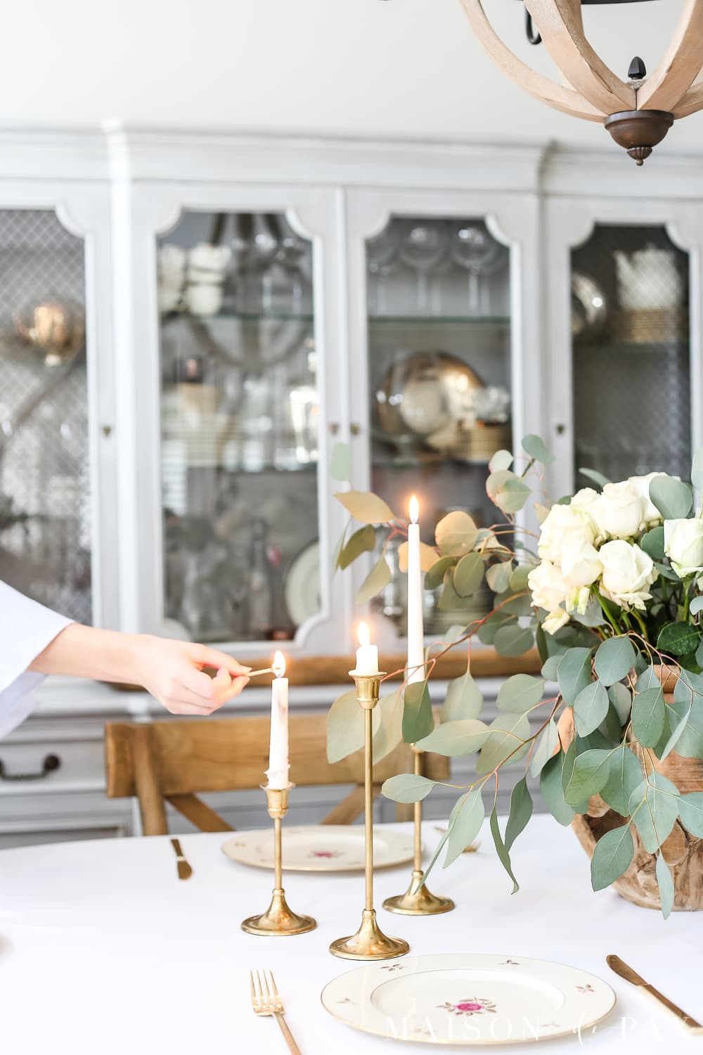 Beautiful brass candlesticks and white roses and eucalyptus centerpiece- Maison de Pax